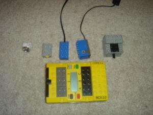 mattone-programmabile-lego-mindstorms-fotografato-vicino-a-tre-sensori-tattile-luminoso-e-di-rotazione-e-ad-un-motore-elettrico.